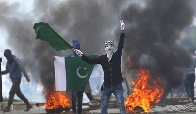 A Kashmiri Muslim protester shows Pakistani flag and shouts anti Indian slogans during a protest after Eid al-Fitr prayers in Srinagar, Indian controlled Kashmir, Monday, June 26, 2017.  Indian forces used tear gas and pellet guns to disperse hundreds of stone-throwing protesters who took to the streets after Eid al-Fitr prayers protesting Indian rule on Monday. (AP Photo/Mukhtar Khan)