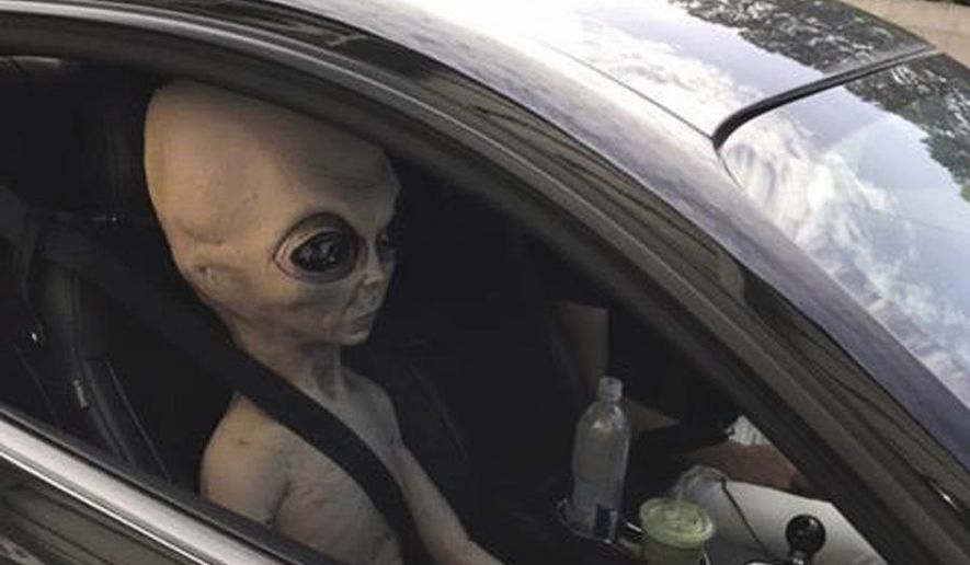 In this Sunday, June 25, 2017 photo provided by the Alpharetta Department of Public Safety an alien figure sits in the passenger seat of a vehicle that was pulled over north of Atlanta, Ga. (Alpharetta Department of Public Safety via AP)