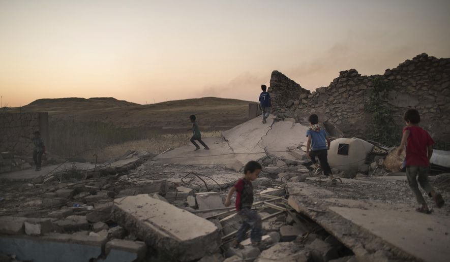 Children play on debris in a neighborhood recently retaken by Iraqi security forces during fighting against Islamic State militants in west Mosul, Iraq, Sunday, June 25, 2017. (AP Photo/Felipe Dana)