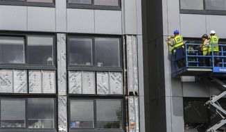Workers remove cladding from Whitebeam Court, in Pendleton, Manchester, Monday June 26, 2017. The list of high-rise apartment towers in Britain that have failed fire safety tests grew to 60, officials said Sunday, revealing the mounting challenge the government faces in the aftermath of London's Grenfell Tower fire tragedy. (Peter Byrne/PA via AP)