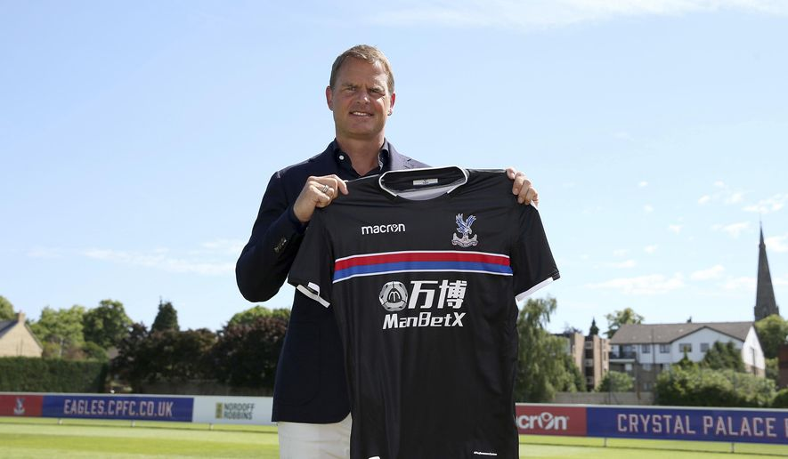 Frank De Boer holds up a team shirt during a photo call after a press conference at Beckenham Training Ground, Kent, Monday June 26, 2017. Former Netherlands defender Frank de Boer has been hired as manager of Crystal Palace, taking his first coaching job in English soccer seven months after getting fired by Inter Milan. (Steven Paston/PA via AP)