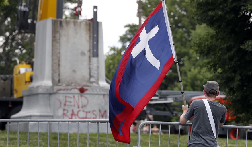Brendan Koch holds a Missouri battle flag used during the Civil War as he watches the removal of a Confederate monument from a city park Monday, June 26, 2017, in St. Louis. As part of an agreement between the city and the Missouri Civil War Museum, the museum will pay for the removal of the monument and store it until a permanent new site is found for it. (AP Photo/Jeff Roberson)