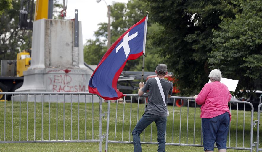 Brendan Koch, left, holds a Missouri battle flag used during the Civil War as he and his mother, Janet Koch, watch the removal of a Confederate monument from a city park Monday, June 26, 2017, in St. Louis. As part of an agreement between the city and the Missouri Civil War Museum, the museum will pay for the removal of the monument and store it until a permanent new site is found for it. (AP Photo/Jeff Roberson)