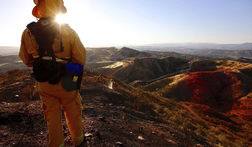Battalion Chief with Pasadena Fire Tony watches his crew as they battle a brush fire in Santa Clarita, Calif., Sunday, June 25, 2017.  The wind-driven brush fire sparked Sunday when a car crashed on a Los Angeles County freeway quickly spread, prompting authorities to temporarily shut down all lanes of a highway and order mandatory evacuations. (Francine Orr/Los Angeles Times via AP) MANDATORY CREDIT