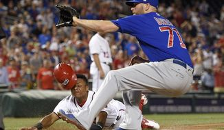 Washington Nationals Wilmer Difo, bottom, slides home on a wild pitch against Chicago Cubs relief pitcher Wade Davis (71) during the ninth inning of a baseball game, Monday, June 26, 2017, in Washington. Diff scored on the play. The Cubs won 5-4. (AP Photo/Nick Wass)