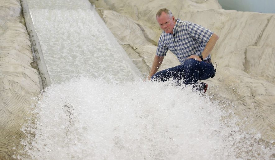 In this Friday, June 16, 2017, photo, hydraulic engineering professor Michael Johnson looks at the water flow on a replica of the Oroville Dam spillway at Utah State University's Water Research Laboratory, in Logan, Utah. California water officials are relying on key hydrology tests being performed on the replica of the spillway to pinpoint what repairs will work best at the tallest dam in the U.S for a spillway that was torn apart in February. (AP Photo/Rick Bowmer)