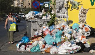 A woman walks past a pile of garbage outside a Pet shop, in Piraeus, near Athens, on Monday, June 26, 2017. Municipality workers have been on strike for almost a week, hindering trash collection across the country. (AP Photo/Petros Giannakouris)