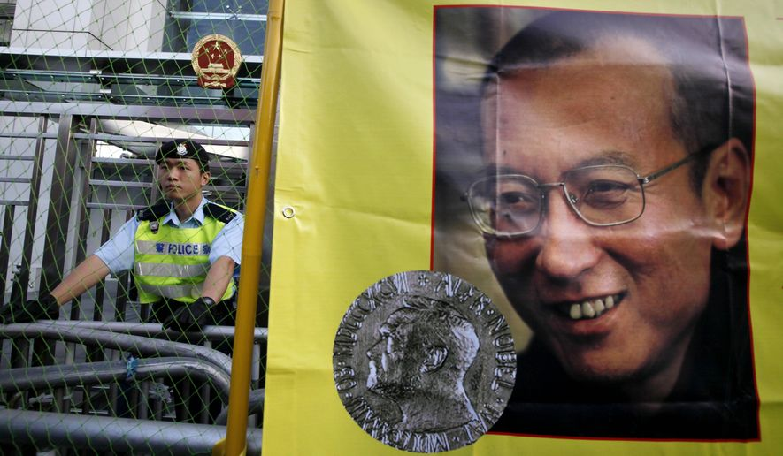 FILE - In this Dec. 5, 2010 file photo, a police officer stands guard beside a picture of jailed Chinese dissident Liu Xiaobo outside the Chinese government liaison office in Hong Kong. Jailed Chinese Nobel peace laureate Liu has been released on medical parole after being diagnosed with late-stage liver cancer, his lawyer said Monday, June 26, 2017. (AP Photo/Kin Cheung, File)