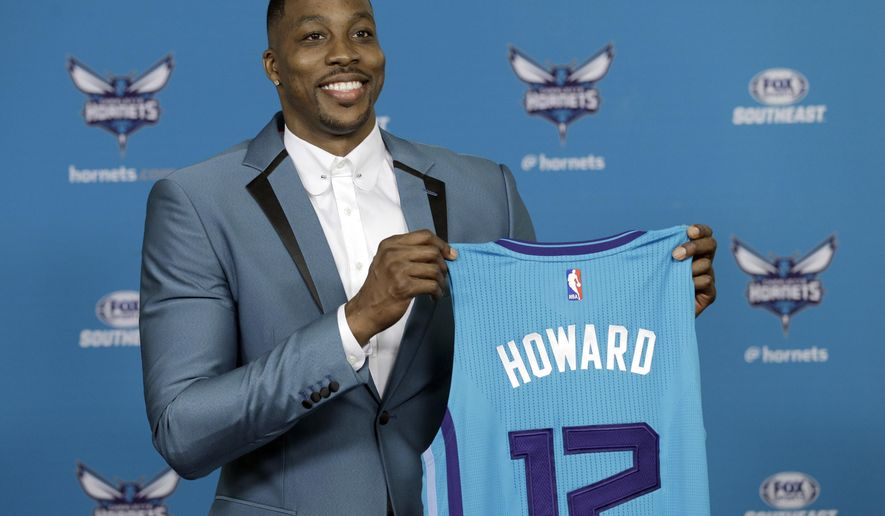 Charlotte Hornets' Dwight Howard poses for a photo holding his new jersey during an NBA basketball news conference in Charlotte, N.C., Monday, June 26, 2017 after being traded to the Hornets by the Atlanta Hawks last week. (AP Photo/Chuck Burton)