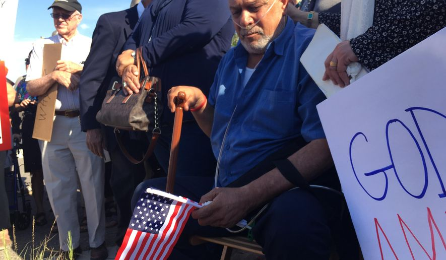 Kadhim Al-bumohammed, center, a 64-year-old Iraqi refugee in the U.S., listens to speakers at an Albuquerque rally in his honor on Monday, June 26, 2017. Around 300 supporters demonstrated outside the Immigration and Customs Enforcement offices in Albuquerque, N.M., in support of Al-bumohammed who may face deportation. Supporters say Al-bumohammed helped train U.S. soldiers going to Iraq and will face death if he's deported. (AP Photo/Russell Contreras)