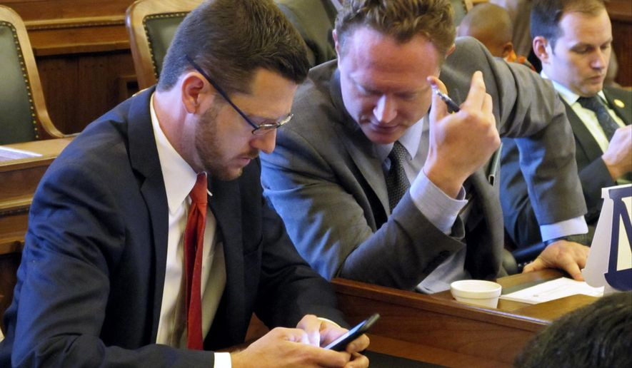Kansas state Reps. John Wilson, left, D-Lawrence, and Tim Hodge, right, D-North Newton, talk during the House's brief session before lawmakers adjourned for the year, Monday, June 26, 2017, at the Statehouse in Topeka, Kan. Wilson said he plans to resign from the Legislature this fall for family reasons. (AP Photo/John Hanna)