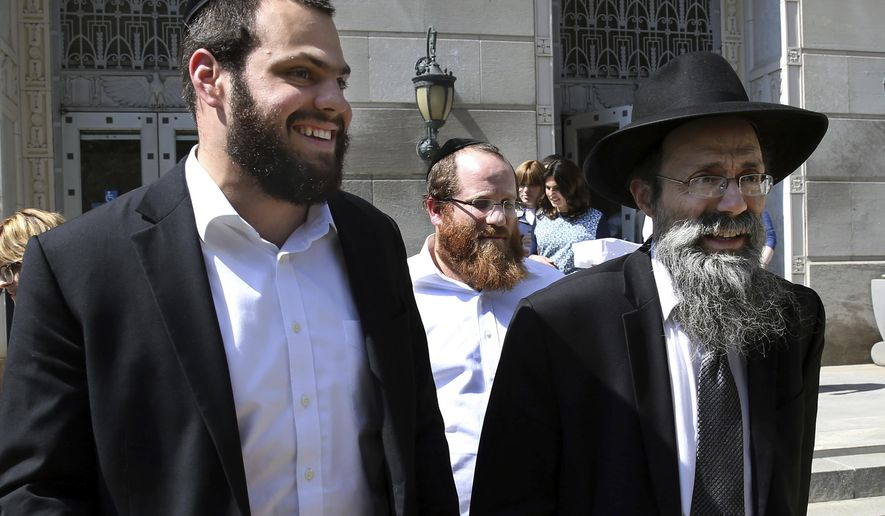 Mordechai Sorotzkin, center, brother of Rabbi Zalmen Sorotzkin, walks outside Federal court after a hearing on charges related to alleged public assistance fraud Monday, June 26, 2017, in Trenton, N.J. Rabbi Zalmen Sorotzkin, a prominent rabbi and several others were arrested in simultaneous federal and state raids Monday morning on charges related to alleged public assistance fraud on a scale rarely seen before in New Jersey, according to law enforcement sources. (AP Photo/Mel Evans)