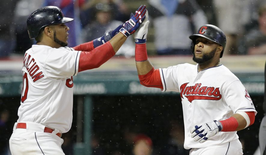 Cleveland Indians' Edwin Encarnacion, left, and Carlos Santana celebrate after both score on Lonnie Chisenhall's two-run single in the sixth inning of a baseball game against the Texas Rangers, Monday, June 26, 2017, in Cleveland. (AP Photo/Tony Dejak)