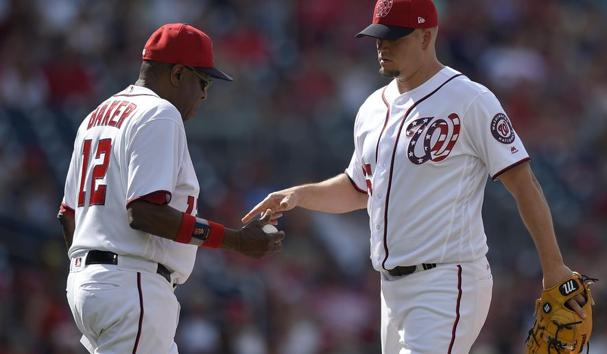 Washington Nationals relief pitcher Joe Blanton, right, is pulled from the game by manager Dusty Baker (12) during the ninth inning of a baseball game against the Cincinnati Reds, Sunday, June 25, 2017, in Washington.  (AP Photo/Nick Wass)