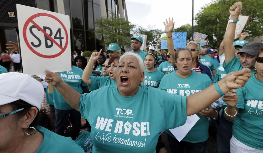"Merced Leyua, center, joins other protesters outside the Federal Courthouse to protest a new Texas ""sanctuary cities"" bill that aligns with the president's tougher stance on illegal immigration, Monday, June 26, 2017, in San Antonio. (AP Photo/Eric Gay)"