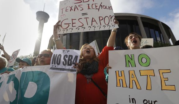 "Marilia Frutuoso, center, joins other protesters outside the Federal Courthouse to protest a new Texas ""sanctuary cities"" bill that aligns with the president's tougher stance on illegal immigration, Monday, June 26, 2017, in San Antonio. (AP Photo/Eric Gay)"