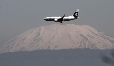 FILE--In this July 9, 2009, file photo, Washington's Mount St. Helens is seen through a layer of smog as an Alaska Airlines plane comes in for a landing at Portland International Airport in Portland, Ore. Alaska Airlines is offering a charter flight off the Oregon coast during the solar eclipse Aug. 21, 2017, that will allow select passengers to view the astronomical event from the sky. The flight will take off at 7:50 a.m. from Portland, Ore., and is by invitation-only for astronomers and other experts. (AP Photo/Don Ryan, file)
