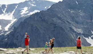 A family strolls the scenic overlook in Colorado's Rocky Mountain National Park. (Associated Press)