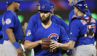 Chicago Cubs starting pitcher Jake Arrieta, center, walks to the dugout after he was pulled from the game during the fifth inning of a baseball game against the Washington Nationals, Tuesday, June 27, 2017, in Washington. The Nationals won 6-1. (AP Photo/Nick Wass)