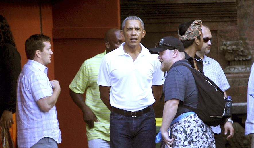 Former U.S. President Barack Obama, center, talks to his staff during his visit at Tirta Empul temple in Bali island, Indonesia, Tuesday, June 27, 2017. Obama and his family arrived last week on the resort island for a vacation in the country where he lived for several years as a child. (AP Photo/Firdia Lisnawati)