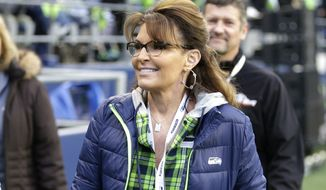 In this Dec. 15, 2016, file photo, Sarah Palin, political commentator and former governor of Alaska, walks on the sideline before an NFL football game between the Seattle Seahawks and the Los Angeles Rams in Seattle. Palin is accusing The New York Times of defamation over an editorial that linked one of her political action committee ads to the mass shooting that severely wounded then-Arizona Congressman Gabby Giffords, according to a lawsuit filed in Manhattan federal court on Tuesday, June 27, 2017. (AP Photo/Scott Eklund, File)
