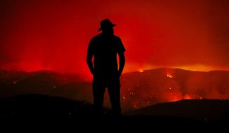 Forrest Scott looks out at the burning Hill Fire from his home off of Huer Huero Road near Santa Margarita, Calif. Monday, June 26, 2017. The property where he lives was surrounded by the flames, but his home and all but one small out building, were saved by Cal Fire crews.  (Joe Johnston/The Tribune (of San Luis Obispo) via AP)