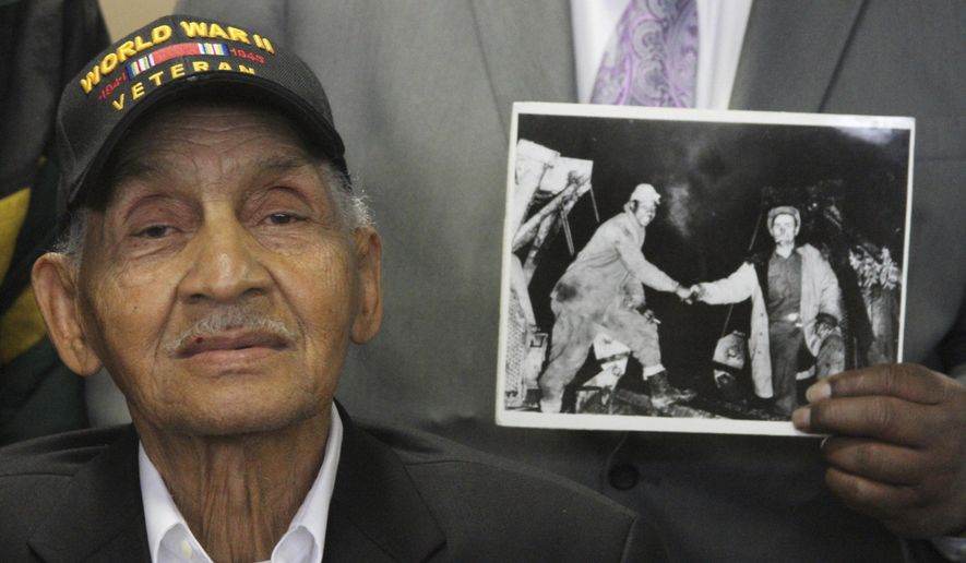 This June 5, 2017, photo shows World War II veteran Leonard Larkins at an event in Anchorage, Alaska, celebrating the 75th anniversary of construction of the Alaska Highway while someone holds an iconic photo of a black and white soldier shaking hands when the two sides building the road met in 1942. Larkins, of New Orleans, was among scores of segregated black soldiers who toiled in North America's harshest weather and terrain to help build a 1,500-mile highway across Alaska and Canada as a supply route during World War II. (AP Photo/Mark Thiessen)