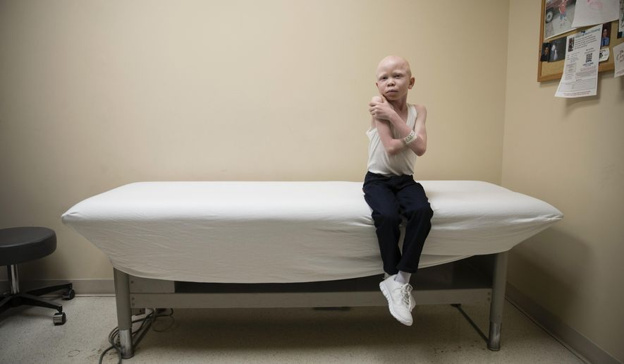 Baraka Cosmas waits to have a plaster cast made of the remainder of his arm at Shriners Hospital for Children in Philadelphia, Monday, March 27, 2017. Cosmas and other children from Tanzania with the hereditary condition of albinism are in the U.S. to receive free surgery and prostheses at the hospital. The children were attacked and dismembered in the belief that their body parts will bring wealth. (AP Photo/Matt Rourke)