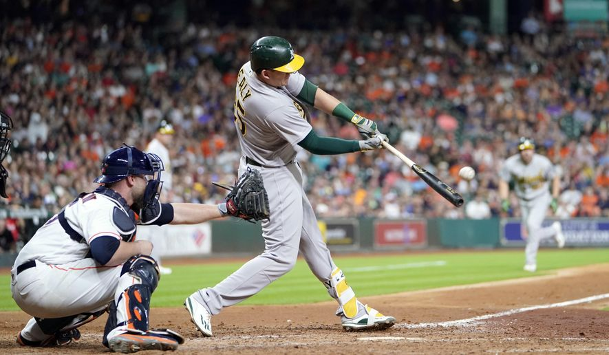 Oakland Athletics' Ryon Healy (25) hits a grand slam as Houston Astros catcher Brian McCann reaches for the pitch during the sixth inning of a baseball game, Tuesday, June 27, 2017, in Houston. (AP Photo/David J. Phillip)