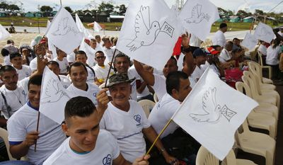 Rebels of the Revolutionary Armed Forces of Colombia, FARC, wave white peace flags during an act to commemorate the completion of their disarmament process in Buenavista, Colombia, Tuesday, June, 27, 2017. The United Nations says it has concluded the disarmament process for individual arms as part of a peace deal between Colombia's FARC rebels and the government. (AP Photo/Fernando Vergara)