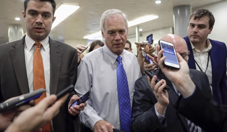 FILE - In this June 22, 2017, file photo, Sen. Ron Johnson, R-Wis., walks through a group of reporters after Republicans released their long-awaited bill to scuttle much of President Barack Obama's Affordable Care Act at the Capitol in Washington. Conservatives and liberals alike in Wisconsin both see hope in Johnson's steadfast refusal to back the current version of the GOP Senate health care bill. (AP Photo/J. Scott Applewhite, File)