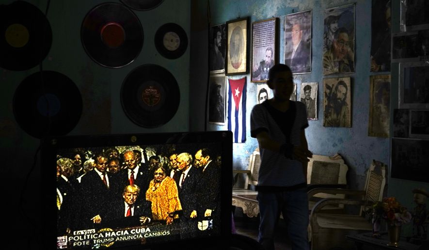 FILE - In this June 16, 2017, file photo, a man walks past a television set showing U.S. President Donald Trump signing the new Cuba policy, in a living room festooned with images of Cuban leaders at a house in Havana, Cuba. President Trump declared he was restoring some travel and economic restrictions on Cuba that were lifted as part of the Obama administration's historic easing. (AP Photo/Ramon Espinosa, File)