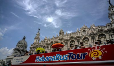 FILE - In this June 17, 2017, file photo, tourists ride a tour bus in front of the Capitolio in Havana, Cuba. Five of 12 private bed-and-breakfast owners in Havana and Cuba's southern colonial city of Trinidad told The Associated Press that they received cancellations after Trump's June 16 announcement of a new policy on Cuba travel. (AP Photo/Ramon Espinosa, File)