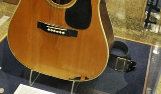FILE - In this April 22, 2013, file photo, a slightly smashed acoustic guitar played by Elvis Presley during the final tour before his death in 1977 is displayed at the National Music Museum in Vermillion, S.D. Memorabilia collector Larry Moss, of Tennessee, is asking an appeals court to overturn a decision that awarded the guitar to the museum at the University of South Dakota. A federal judge ruled this year the museum could keep the guitar after Moss claimed he was the rightful owner. A three-judge panel from the 8th Circuit Court of Appeals will rule on the case. (AP Photo/Dirk Lammers, File)
