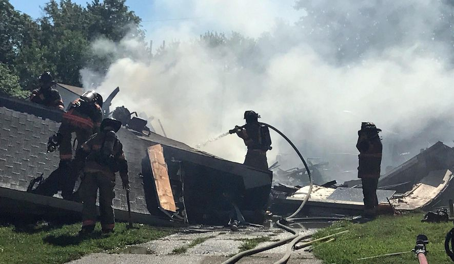 Firefighters work at the scene after an explosion and fire destroyed a home, Tuesday, June 27, 2017, in Evansville, Ind. Authorities say at least three people were injured. The cause of the explosion wasn't immediately known. (Sam Owens/Evansville Courier & Press via AP)