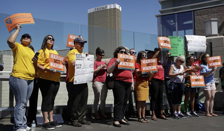People protest with the Trump International hotel in the background, Tuesday, June 27, 2017, in Las Vegas. Union officials in Nevada, community members and others gathered Tuesday at a pedestrian bridge over the Las Vegas Strip to urge Republican U.S. Sen. Dean Heller to continue to oppose the current GOP health care bill. (AP Photo/John Locher)