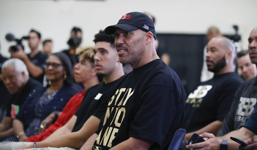 """FILE - In this June 23, 2017, file photo, LaVar Ball, center, father of Los Angeles Lakers draft pick Lonzo Ball, listens to his son during the NBA basketball team's news conference in El Segundo, Calif. LaVar and Lonzo appeared on """"WWE Raw"""" June 26, 2017.  (AP Photo/Jae C. Hong, File)"""