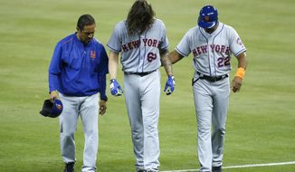 New York Mets' Robert Gsellman (65) is helped off the field by first base coach Tom Goodwin (22) and a trainer during the fourth inning of a baseball game against the Miami Marlins, Tuesday, June 27, 2017, in Miami. Gsellman grabbed the back of his left thigh as he approached first base and grimaced in pain. He was replaced on the mound by Paul Sewald in the bottom of the fourth inning. (AP Photo/Wilfredo Lee)