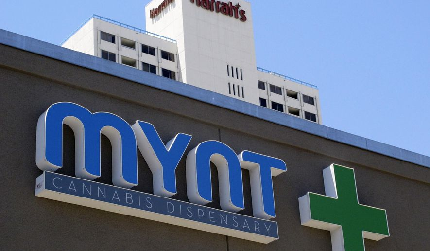 FILE- This June 21, 2017, file photo shows a sign on the Mynt Cannabis Dispensary across the street from Harrah's hotel-casino in downtown Reno, Nev. The Mynt is one of at least four medical marijuana dispensaries in Reno that have received the necessary local licenses and are ready to start selling marijuana for recreational use on July 1 as long as they get their anticipated state license. (AP Photo/Scott Sonner, File)