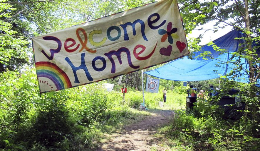 FILE--In this June 28, 2016, file photo, a sign welcomes people to the gathering of the Rainbow Family of Living Light in Mount Tabor, Vt. Federal prosecutors and judges are setting up a temporary court in remote eastern Oregon to handle citations against any attendees at the Rainbow Family of Living Light annual counter-culture gathering. The get-together in the Malheur National Forest set to begin later this week is expected to attract up to 20,000 campers and has already created tensions in this rural community. (AP Photo/Wilson Ring, file)