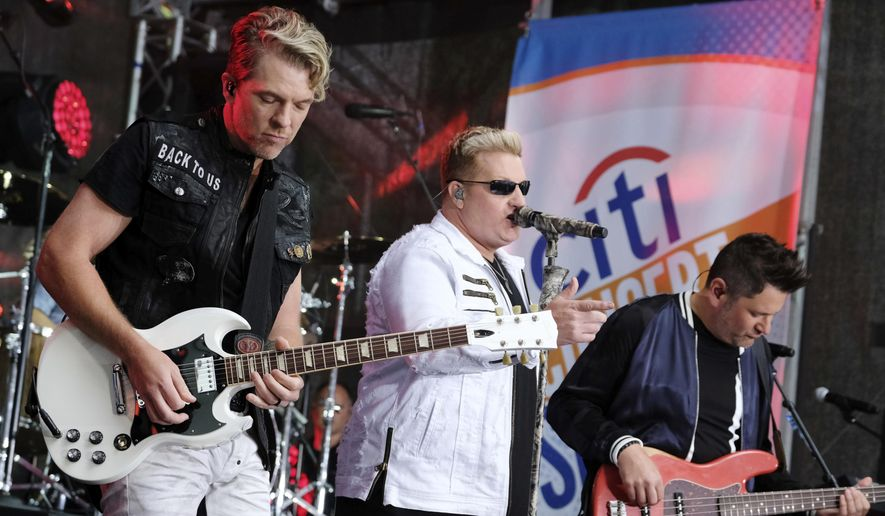 """In this May 22, 2017, file photo, Rascal Flatts band members, from left, Joe Don Rooney, Gary LeVox and Jay DeMarcus perform on NBC's """"Today"""" show at Rockefeller Plaza in New York. The band surprised a bride and groom in Watertown, Wisconsin, on Saturday, June 24, 2017. (Photo by Charles Sykes/Invision/AP, File)"""