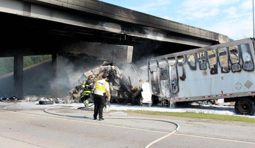 This photo provided by the Jonesboro Police Department shows emergency personnel at the scene Tuesday, June 27, 2017, where a tractor-trailer rig ran into a overpass on northbound Interstate 555 in Jonesboro, Ark. A police spokesman said the truck driver was killed in the accident. (Paul Holmes/Jonesboro Police Department via AP)
