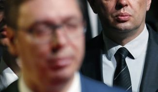 In this photo taken Friday, March 24, 2017, a former Labor Minister Aleksandar Vulin, right, stands behind Serbian President Aleksandar Vucic, in Belgrade, Serbia. Serbia's future first woman and openly gay prime minister Ana Brnabic has proposed the staunchly pro-Russian official, and former Labor Minister Aleksandar Vulin as the defense minister, damping hopes in the west that her nomination signals the country's shift away from Moscow's influence. (AP Photo/Darko Vojinovic)