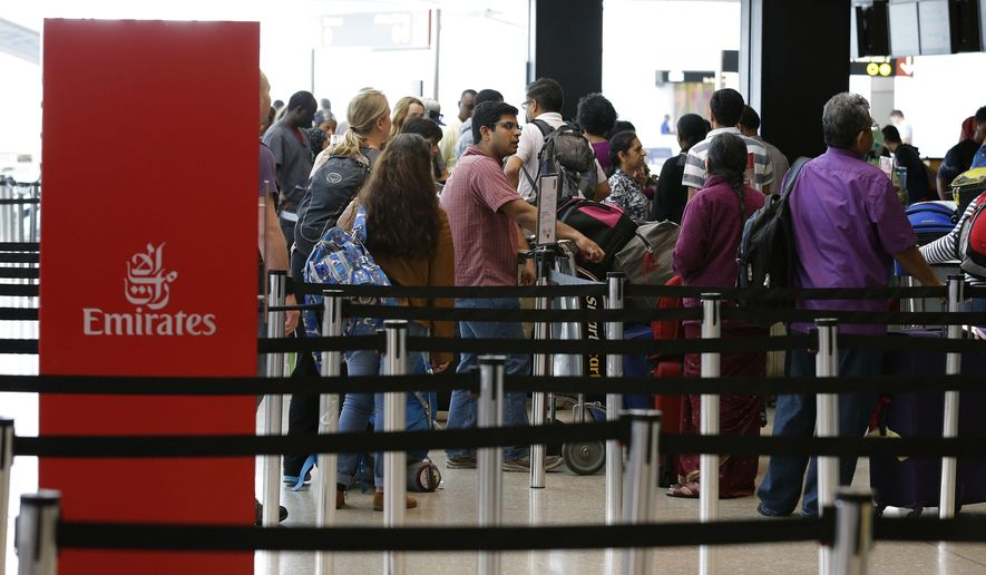 "Travelers wait in line near an Emirates ticket counter at the Seattle-Tacoma International Airport, Monday, June 26, 2017, in Seattle. The U.S. Supreme Court said Monday that President Donald Trump's travel ban on visitors from Iran, Libya, Somalia, Sudan, Syria and Yemen can be enforced if those visitors lack a ""credible claim of a bona fide relationship with a person or entity in the United States,"" and that justices will hear full arguments in October 2017. (AP Photo/Ted S. Warren)"