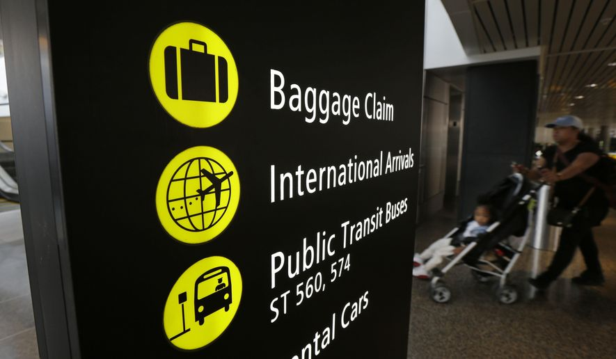 """A woman pushes a stroller near a sign for international arrivals at the Seattle-Tacoma International Airport, Monday, June 26, 2017, in Seattle. The U.S. Supreme Court said Monday that President Donald Trump's travel ban on visitors from Iran, Libya, Somalia, Sudan, Syria and Yemen can be enforced if those visitors lack a """"credible claim of a bona fide relationship with a person or entity in the United States,"""" and that justices will hear full arguments in October 2017. (AP Photo/Ted S. Warren) **FILE**"""