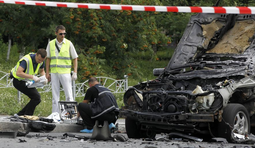 Forensic experts examine the wreckage of a  car in Kiev, Ukraine, Tuesday, June 27, 2017. Ukrainian authorities say that a senior military intelligence officer has been killed in a car bomb in the country's capital. Police say that the driver of a luxury car has been killed instantly as the vehicle blew up at a Kiev intersection. (AP Photo/Sergei Chuzavkov)