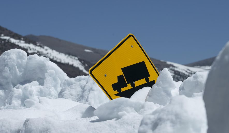 FILE - In this Tuesday, June 6, 2017 file photo, snow more than six feet deep nearly covers a warning sign alongside Highway 120 near Yosemite National Park, Calif. Drivers will be able to cross the Sierra Nevada through Yosemite National Park beginning Thursday, June 29, in the latest opening for the mountain in more than three decades, officials said Tuesday. (AP File Photo/Rich Pedroncelli)
