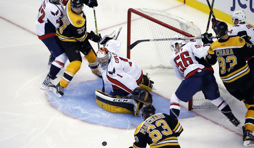 Washington Capitals goalie Pheonix Copley (1) protects the net against Boston Bruins left wing Brad Marchand (63) while Bruins center Patrice Bergeron (37) and Bruins defenseman Zdeno Chara (33) try to get position on Capitals right wing Joel Ward (42) and Capitals defenseman Patrick Wey (56) in the third period of an NHL preseason hockey game in Boston, Wednesday, Sept, 24, 2014. The Bruins won 2-0. (AP Photo/Elise Amendola)