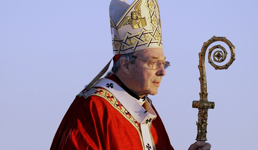 FILE - In this July 15, 2008, file photo, Cardinal George Pell walks onto the stage for the opening mass for World Youth Day in Sydney, Australia. Australian police say they are charging Pell with historical sexual assault offenses. (AP Photo/Rick Rycroft, File)