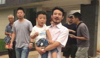 This image taken from video shows Chinese labor activists Hua Haifeng, center, carrying his son Bobo, and Li Zhao, second from left, leave a police station after being released in Ganzhou in southern China's Jiangxi Province, Wednesday, June 28, 2017. Chinese authorities have released three activists, including Hua and Li, who had been detained after investigating labor conditions at a factory that produced shoes for Ivanka Trump and other brands. (AP Photo/Gerry Shih)